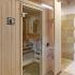 Badezimmer Sauna mit Dusche - Ansicht von schräg links, Glastüre und Regal