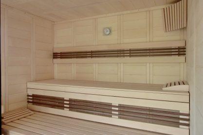 Massivholz-Sauna in Fichte mit Glasfront und Einrichtung in Nussbaum-Design