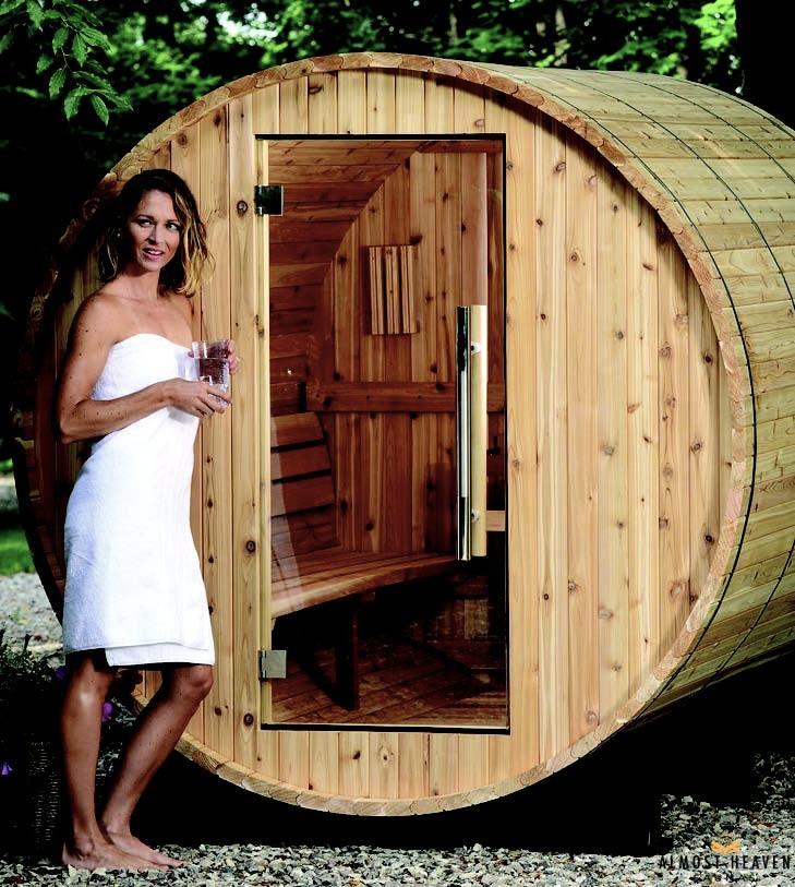 Eine Frau steht neben einer Fass-Sauna